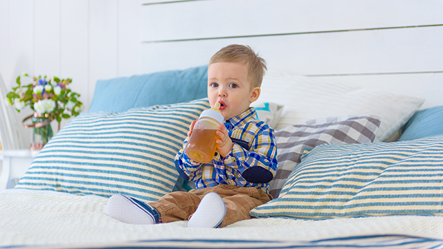 Baby boy sitting on the bed and drinking juice with bottle of nipple.; Shutterstock ID 1314714614; Purchase Order: N/A