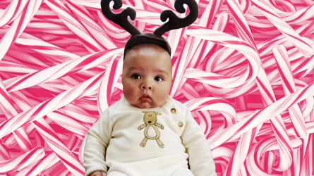 christmas baby girl with antlers against