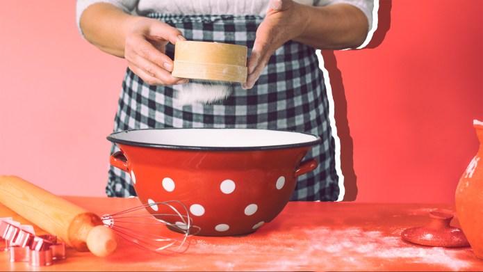 Woman sieving flour in kitchen