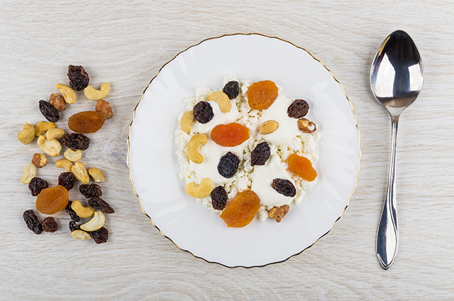 Cottage cheese, sour cream, dried fruits and nuts in plate, spoon, heap of fruits and nuts on wooden table. Top view; Shutterstock ID 1156873687; Purchase Order: N/A