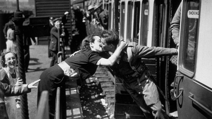Couple kissing at train station