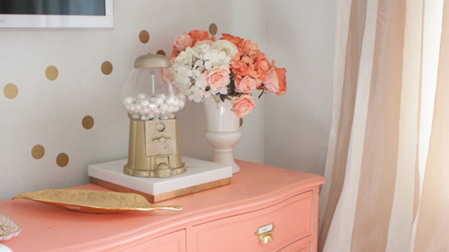 Gold gumball machine next to flowers on dresser