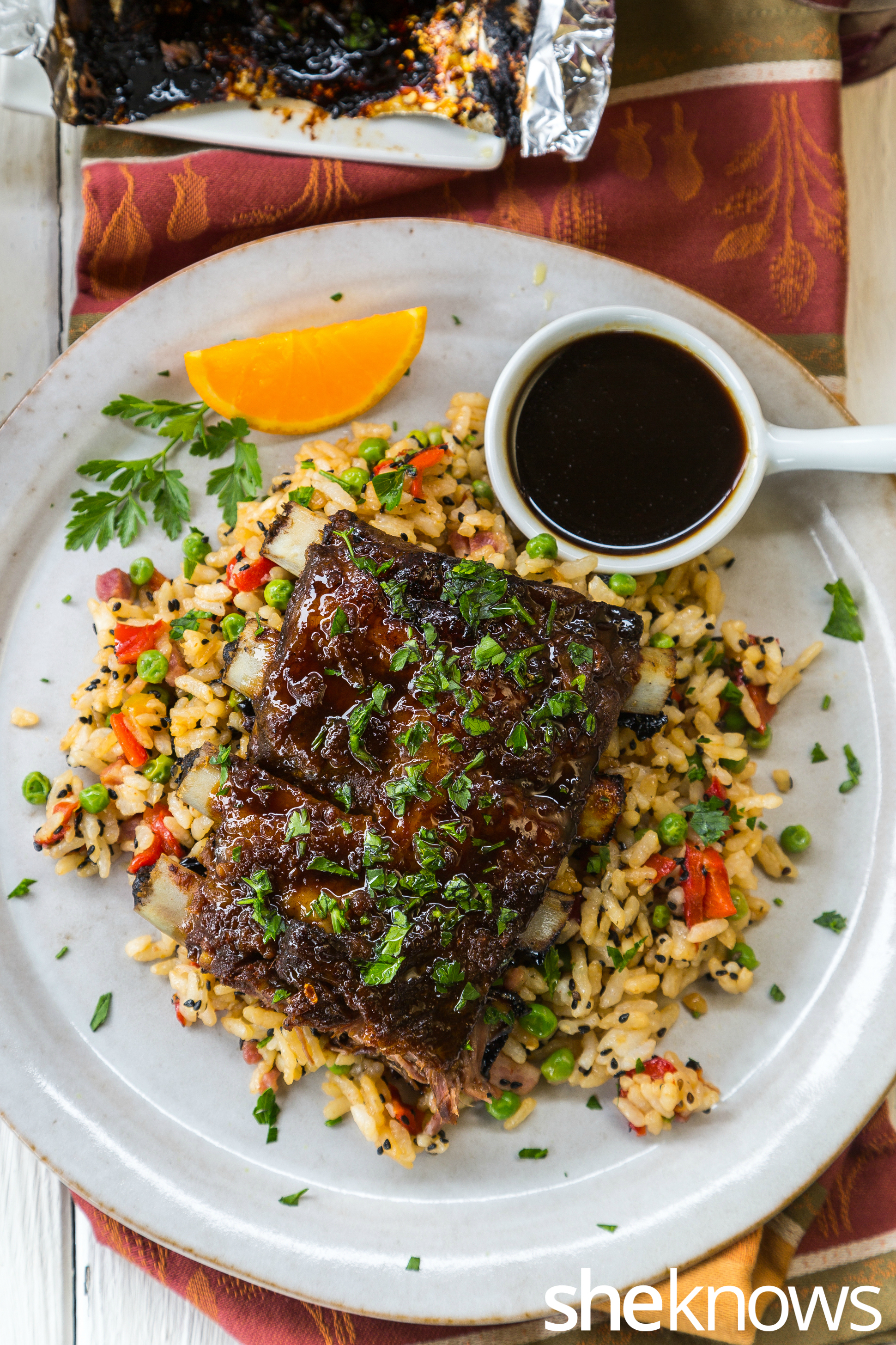 Baked orange-soy pork ribs with fried rice on plate