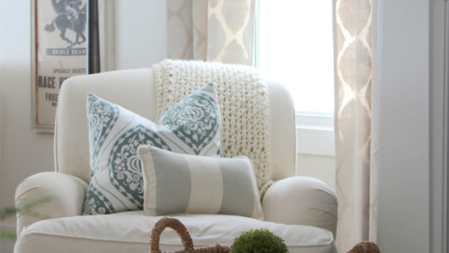 Comfy chair with linens and painted curtains