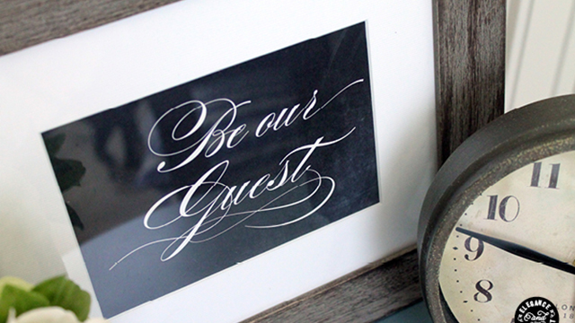 Be Our Guest frame on bedside table with clock
