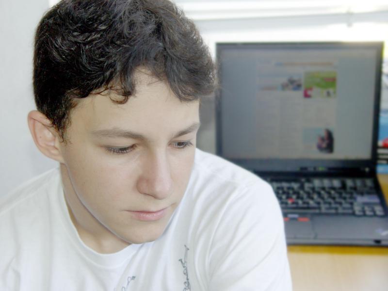Teen facing away from laptop