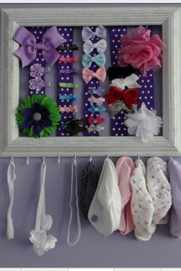 An old frame, ribbon, and hooks keep baby's hair bows, ribbons and hats neatly organized.