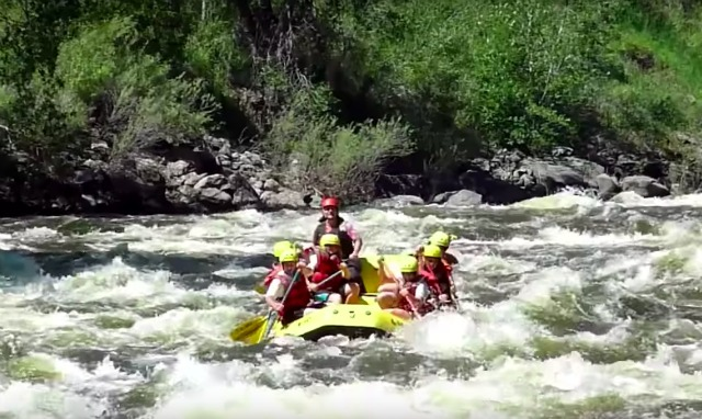 Kids go river rafting with a counselor at Camp Cheley in Colorado.