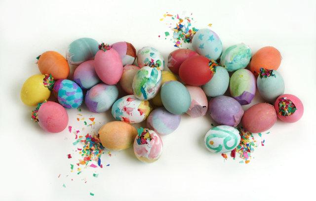 Dozens of confetti eggs (cascarones) on a white background
