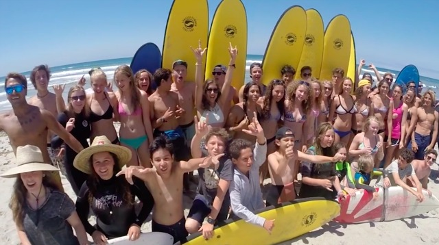 Campers from Endless Summer Surf Camp pose in front of their surf boards on the beach.