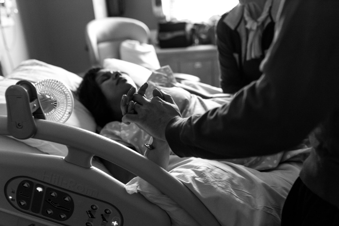 Childbirth photography: A husband holds his wife's hand as she pushes through labor