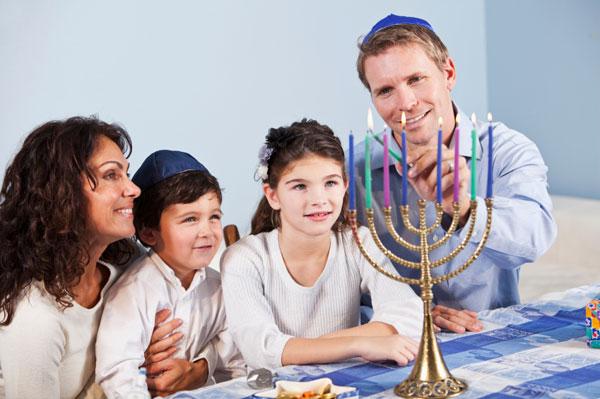 Family lighting the menorah for Hanukkah