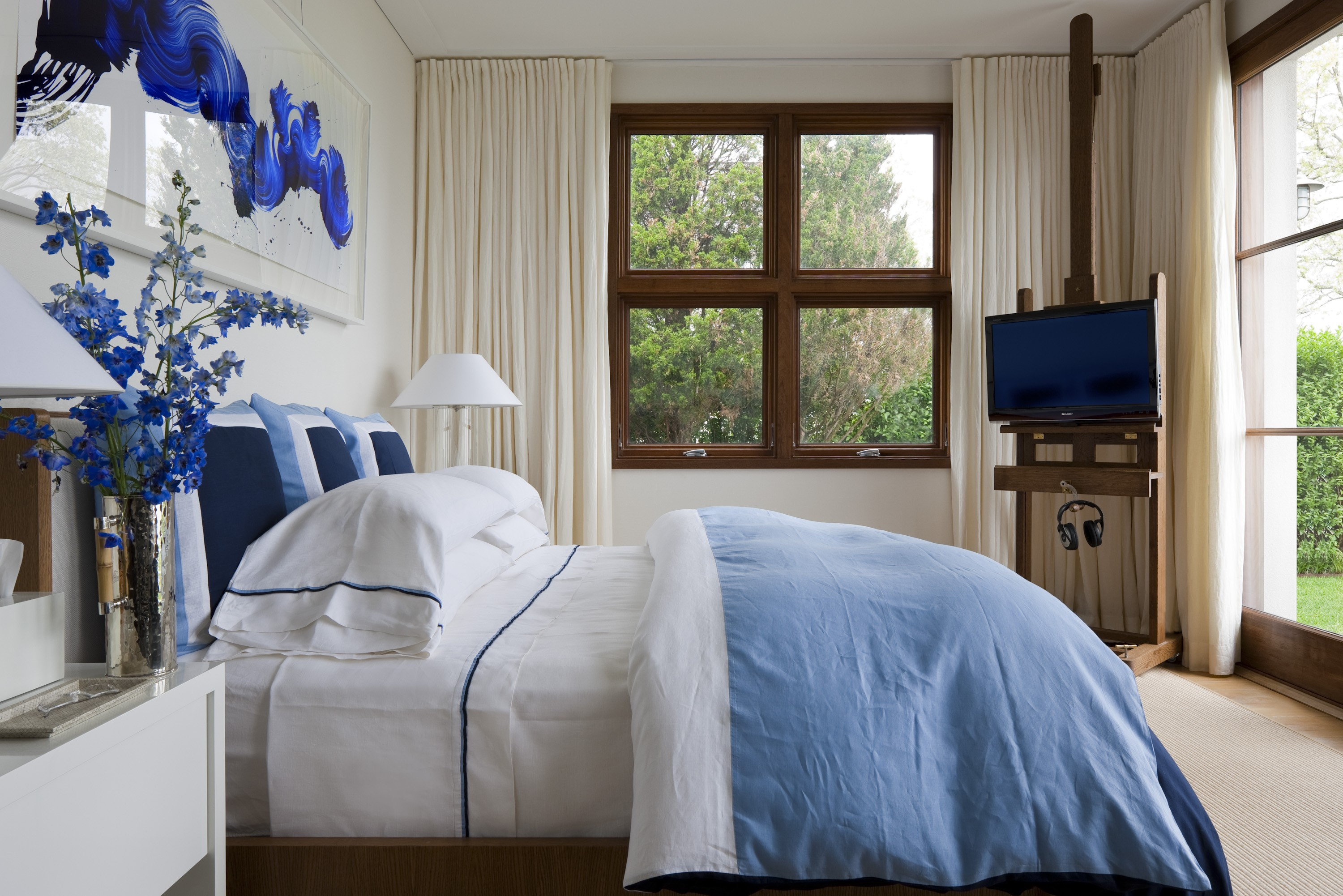 White room with blue pillows and blue artwork
