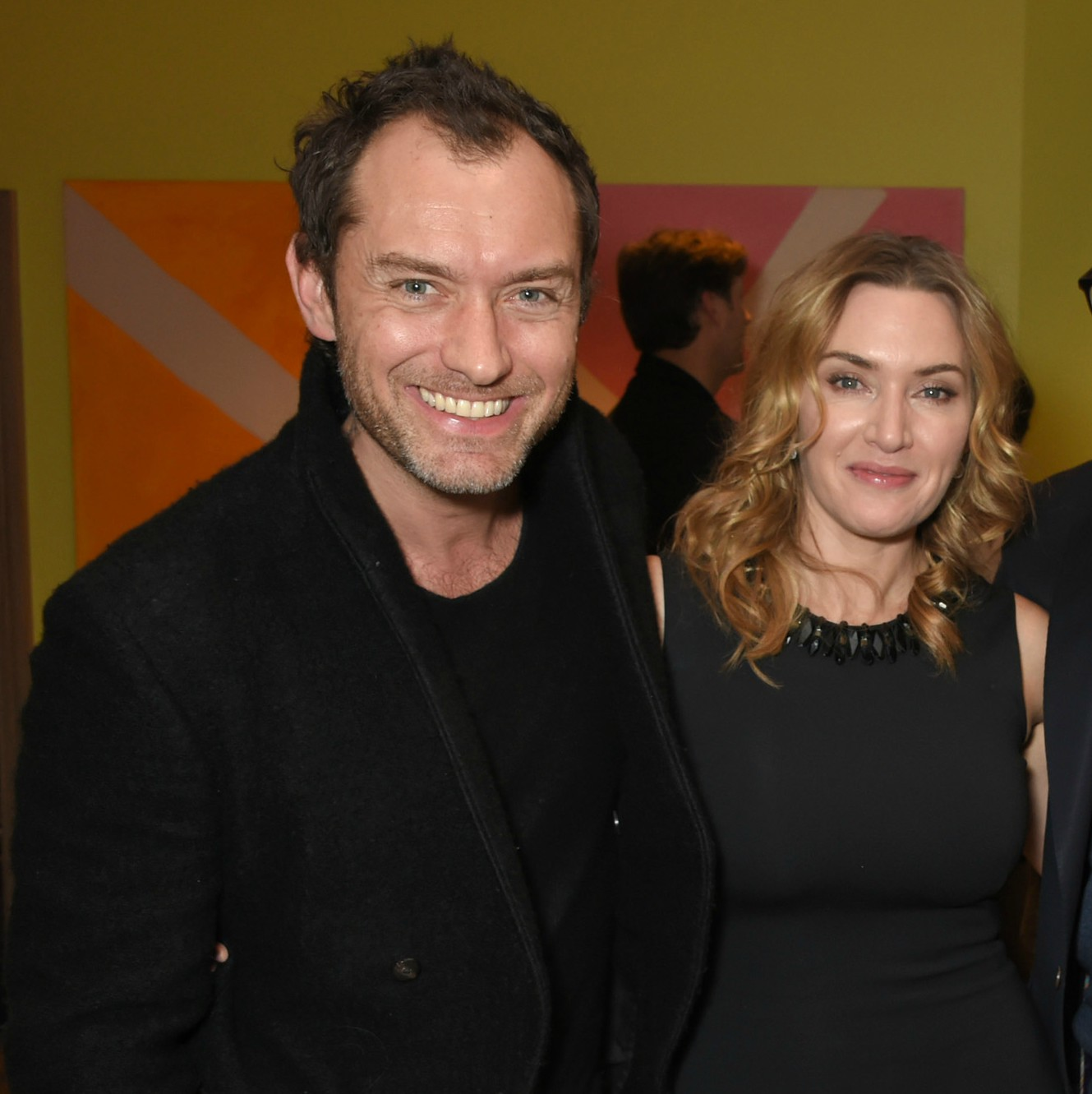 JUde Law and Kate Winslet smiling with their arms around one another at a special screening of 'Wonder Wheel'