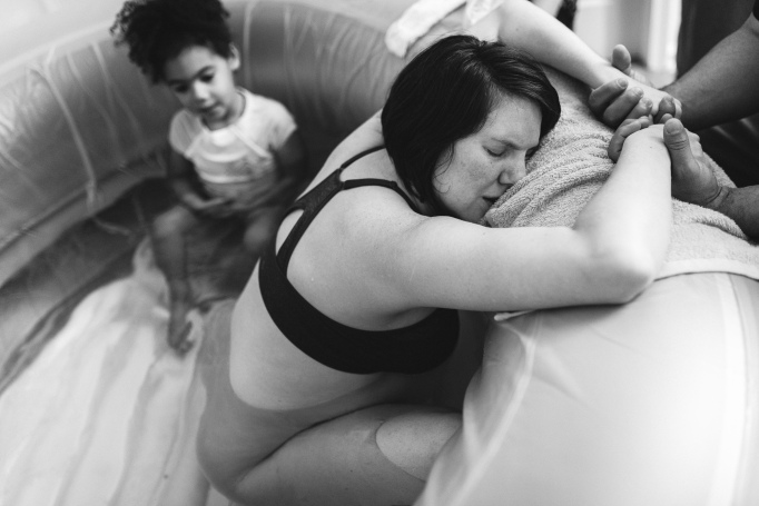 Childbirth photography: A daughter joins her mother in an inflatable tub during labor