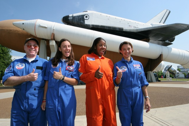 Kids give a thumbs up in front of a space craft at Space Camp in Huntsville, Alabama.