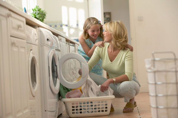 In the laundry room Mother and daughter doing laundry