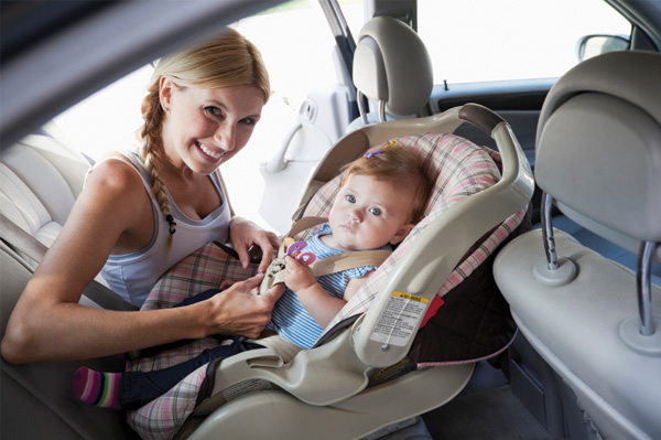 Mother putting child in car seat