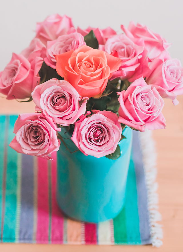 Pink roses in blue vase with one orange rose