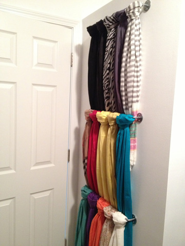Towel rods make for perfect scarf storage behind a closet door.