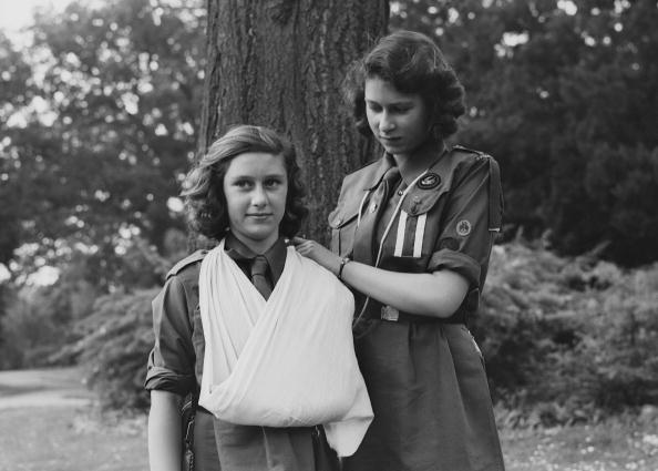 Princess Elizabeth places Princess Margaret's arm in a sling