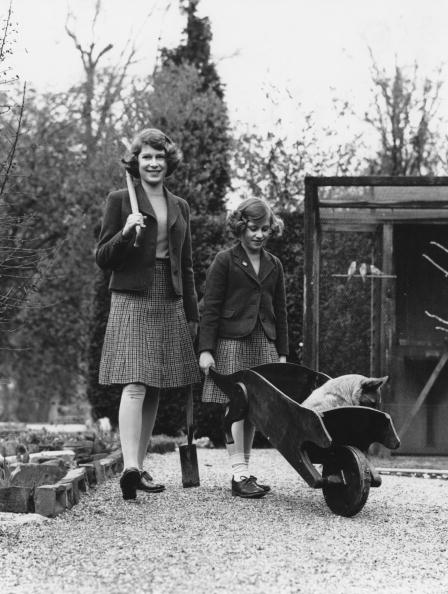 Princess Elizabeth (now Queen Elizabeth II, left) and her younger sister Princess Margaret Rose (1930-2002) in their garden at the Royal Lodge in Windsor Great Park, April 1940. The passenger in the wheelbarrow is a corgi named Carol