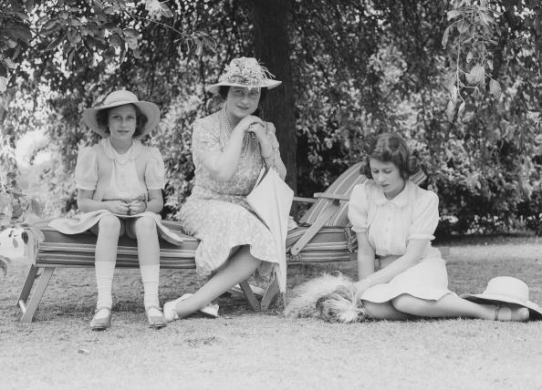The Queen Mother (1900-2002). Princess Elizabeth and Princess Margaret sitting in the garden at Windsor Castle, England on July 8, 1941