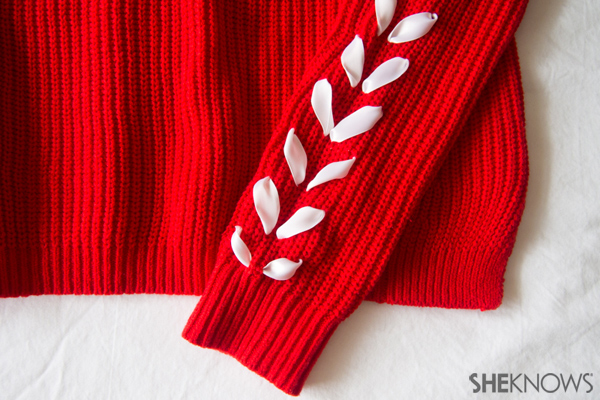 Embellished sweater with ribbons sewn into the arms