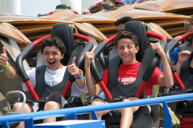 Kids at Thrill Coaster Tours camp smile as they head out on a rollercoaster.