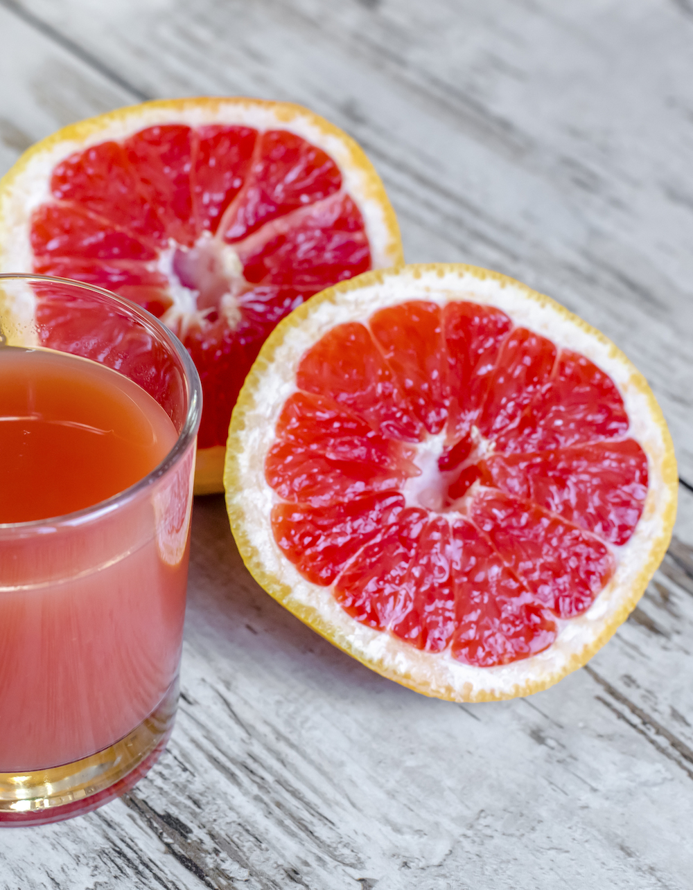 Sliced grapefruit and glass of grapefruit juice on wood