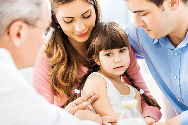 Small child with parents getting immunization shot