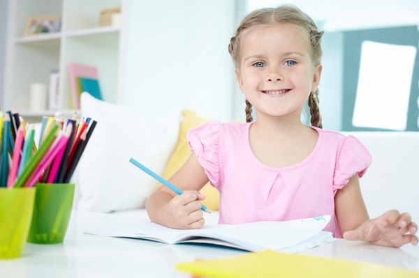 Smiling girl doing school project