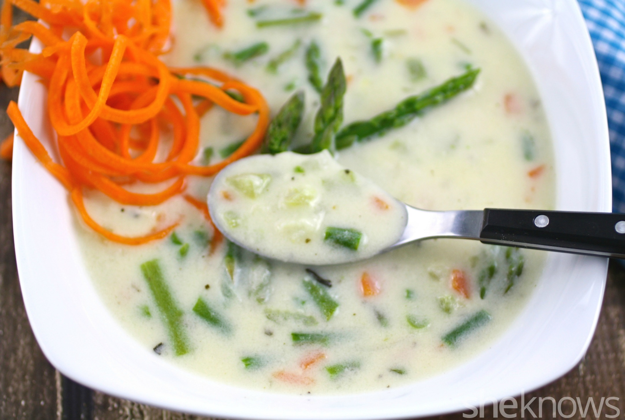Dig into this bowl of cheesy asparagus chowder with carrot curl garnish