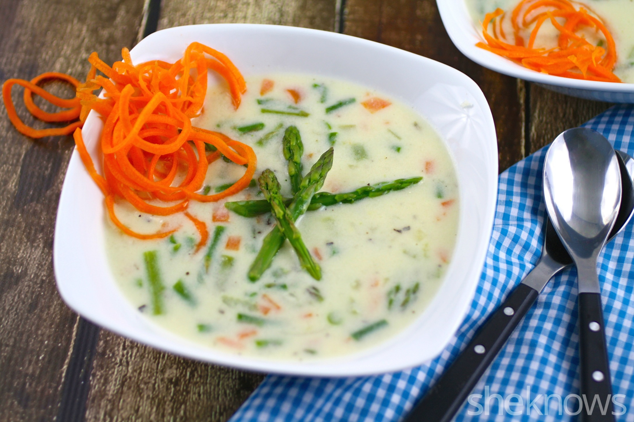 Warm up with a bowl of cheesy asparagus chowder with carrot curl garnish