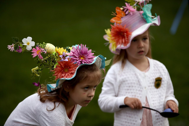 Two little girls wear ornate Easter hats while playing a game of egg roll