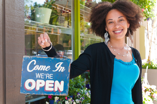Woman holding open sign for her new business