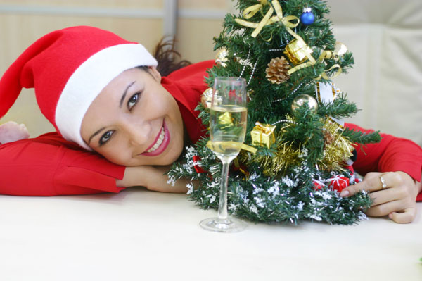Woman with champange and christmas tree