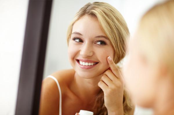 young woman applying skin cream