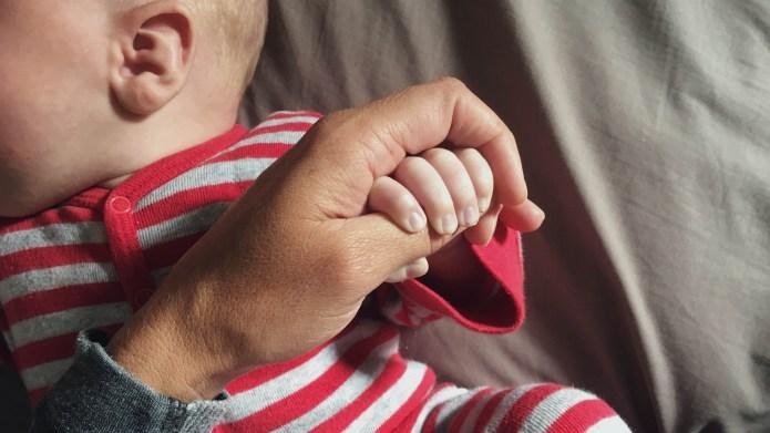 Infant hand holding onto mothers finger