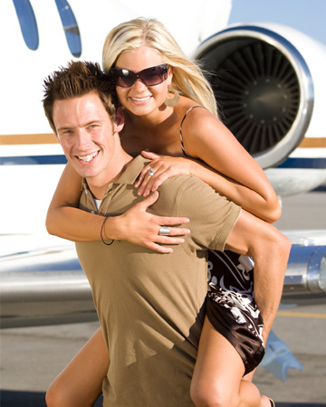 Affluent couple in front of private jet
