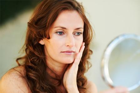 Aging woman looking in mirror