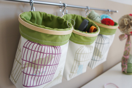 Embroidery hoops and fabric mounted on a hanging system make this toy storage easily accessible for little ones.