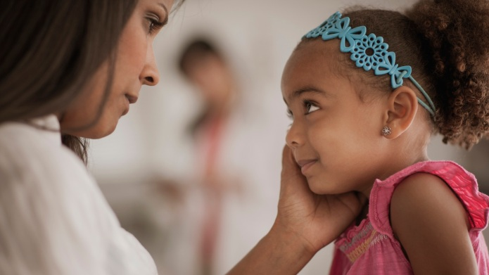 Mother comforting daughter in doctor's office