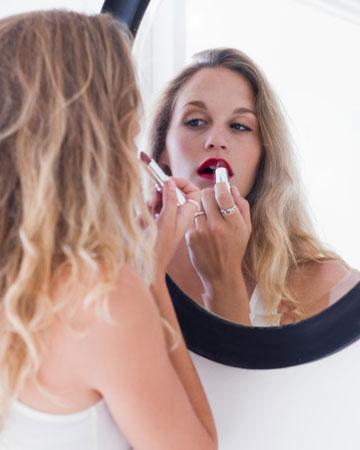 Woman applying red lipsctik in mirror