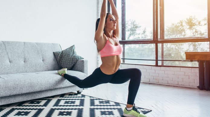 Woman doing lunges in living room