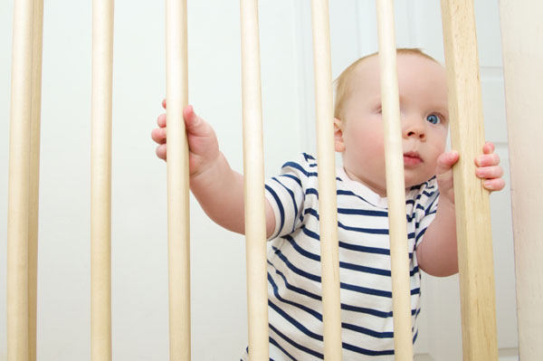 Boy toddler standing behind baby safe gate.
