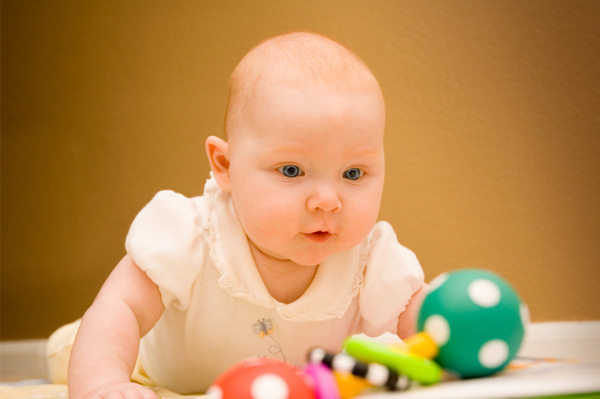 Baby playing with rattle and toys during tummy time