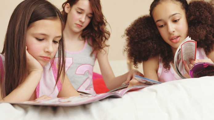 Three girls (10-12) reading magazines, close-up