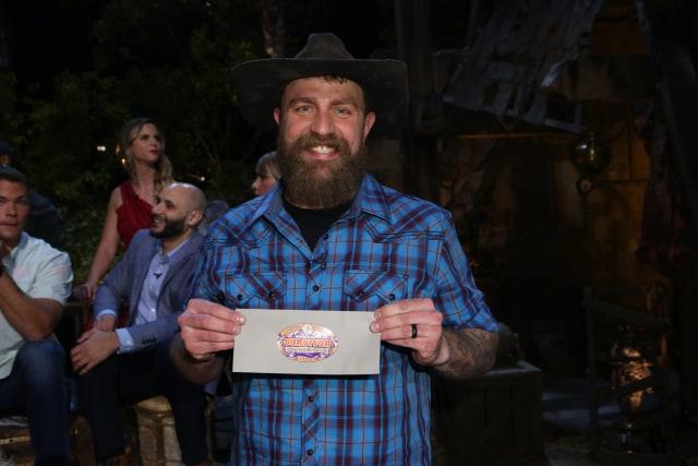 Ben Driebergen holds his $1 million check after winning Survivor: Heroes Vs. Healers Vs. Hustlers