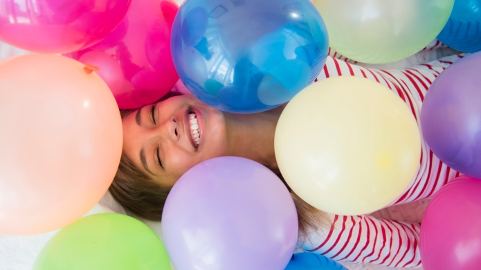 Mixed race woman playing in balloons